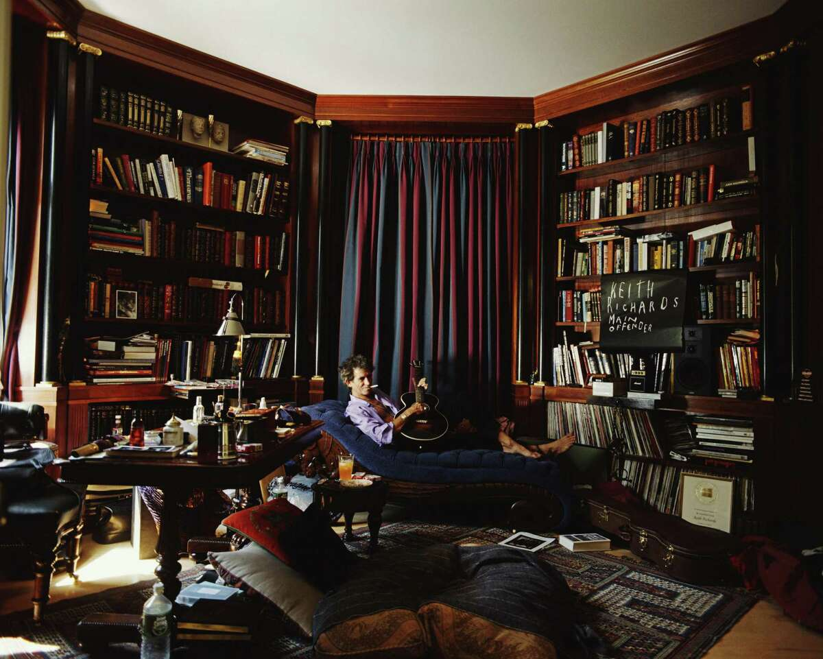 English guitarist Keith Richards of the Rolling Stones playing a guitar on a chaise longue in his library, circa 1995. (Photo by Christopher Simon Sykes/Hulton Archive/Getty Images)