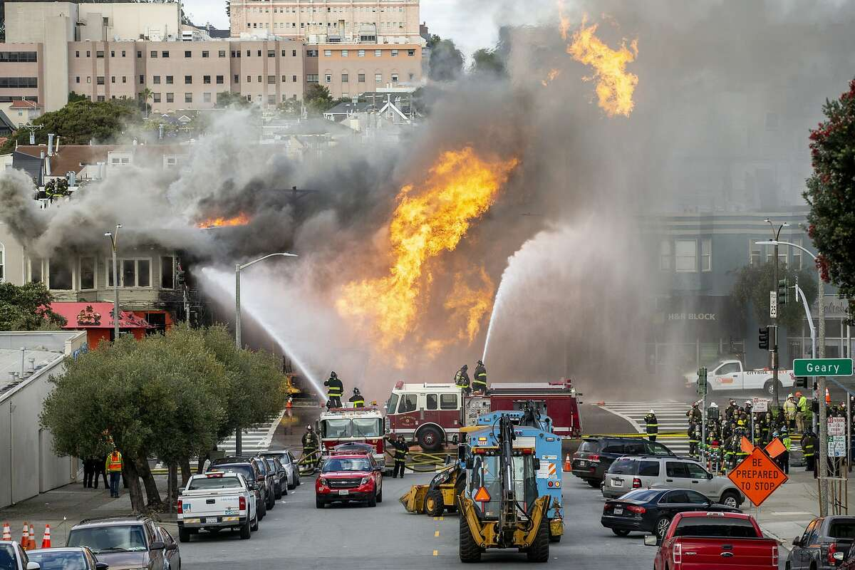 Firefighters battle a fire following an explosion at Geary boulevard and Parker Avenue on Wednesday, Feb. 6, 2019, in San Francisco, Calif.
