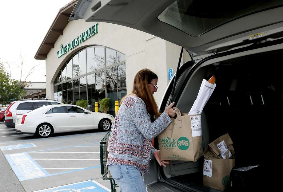 Debi LaBell loads groceries into her minivan at the Whole Foods Market in Redwood City, Calif., on Saturday, January 26, 2019. LaBell, an independent contractor, works for grocery delivery service Instacart on weekends for extra money. She is upset  about a way Instacart has changed payments which she says results in lower wages. Photo: Yalonda M. James / The Chronicle