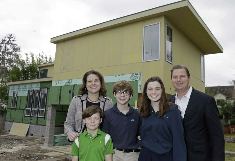 Stacey and Scott Butler and their children Nate, 10, Bryce, 13, and Chloe, 16, pose in front of their Braeswood Place home that is under construction. Their original home on this site was flooded in Hurricane Harvey and they decided that it was better to demolish and build new, rather than repair their midcentury modern home designed by Lars Bang. Photo: Melissa Phillip, Houston Chronicle / Staff Photographer / © 2019 Houston Chronicle