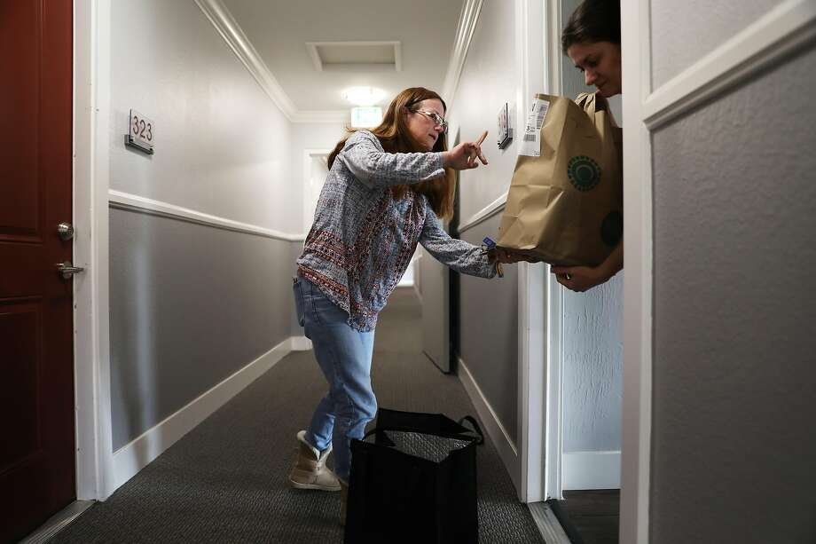 Debi LaBell delivers groceries to Marianna Ksovreli in Redwood City, Calif., on Saturday, January 26, 2019. LaBell, an independent contractor, works for grocery delivery service Instacart on weekends for extra money. She is upset  about a way Instacart has changed payments which she says results in lower wages. Photo: Yalonda M. James, The Chronicle