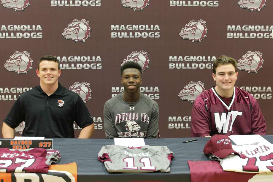 Magnolia football players Hayden Kelly, Darren Battle and Cole Vairin pose for a photo at their Signing Day ceremony on Wednesday. Photo: Jon Poorman / Staff