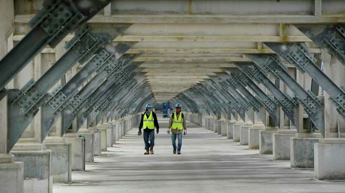 Workers walk along beneath the main pipe rack at Cameron LNG Wednesday, Feb. 6, 2019, in Hackberry, LA. More than 8,000 people are working day and night to bring the liquefied natural gas plant's first production unit into operation over the next few months.