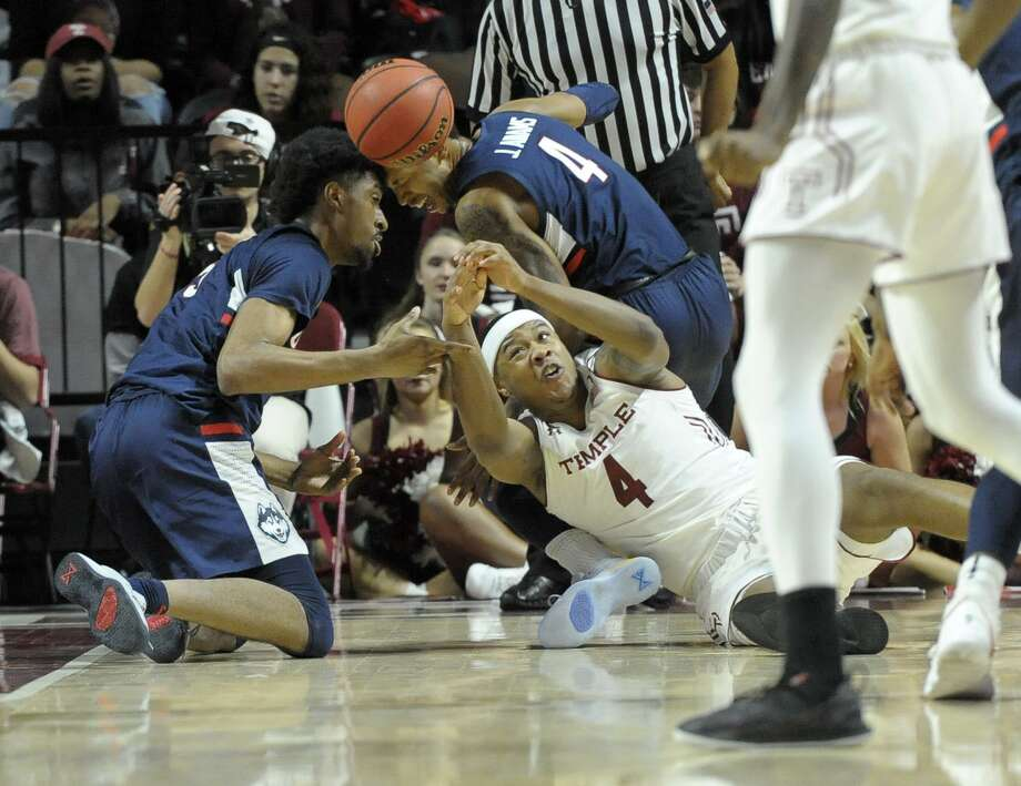 Temple's J.P. Moorman II (4) reaches for a loose ball in front of UConn's Jalen Adams (4) and Isaiah Whaley (5) on Wednesday in Philadelphia. Adams suffered a Grade 2+ MCL sprain on the play when Moorman rolled up his leg. UConn announced on Friday that Adams will miss 4-6 weeks, potentially ending his UConn career. Photo: Michael Perez / Associated Press / FR168006 AP