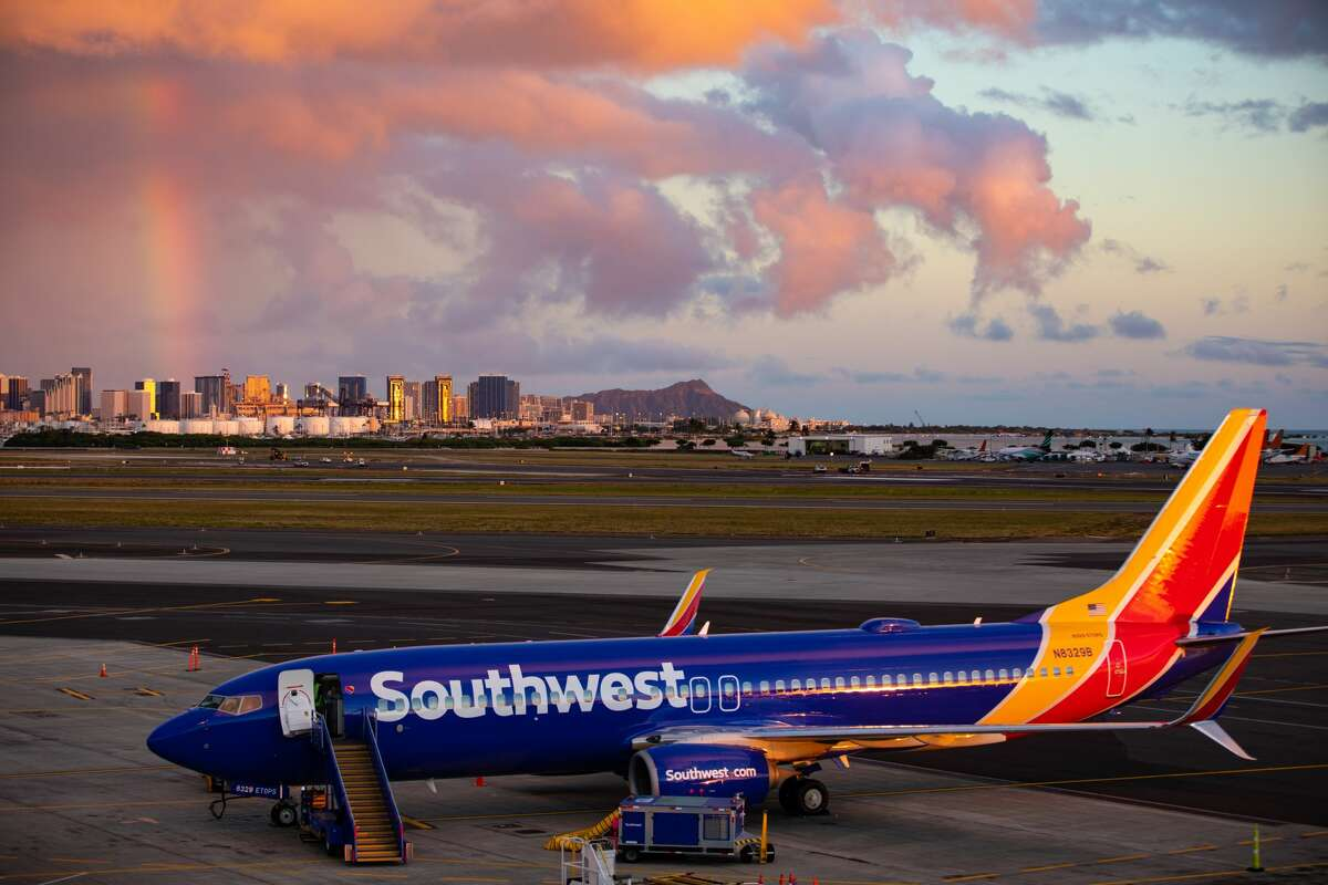 Southwest Airlines Boeing 737-800 at Daniel K. Inouye International Airport-- with Diamond Head and a rainbow in the backgroud