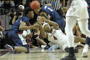 Temple's J.P. Moorman II (4) reaches for a loose ball in front of Connecticut Jalen Adams (4) and Isaiah Whaley (5) during the first half of an NCAA college basketball game, Wednesday, Feb. 6, 2019, in Philadelphia. (AP Photo/Michael Perez)