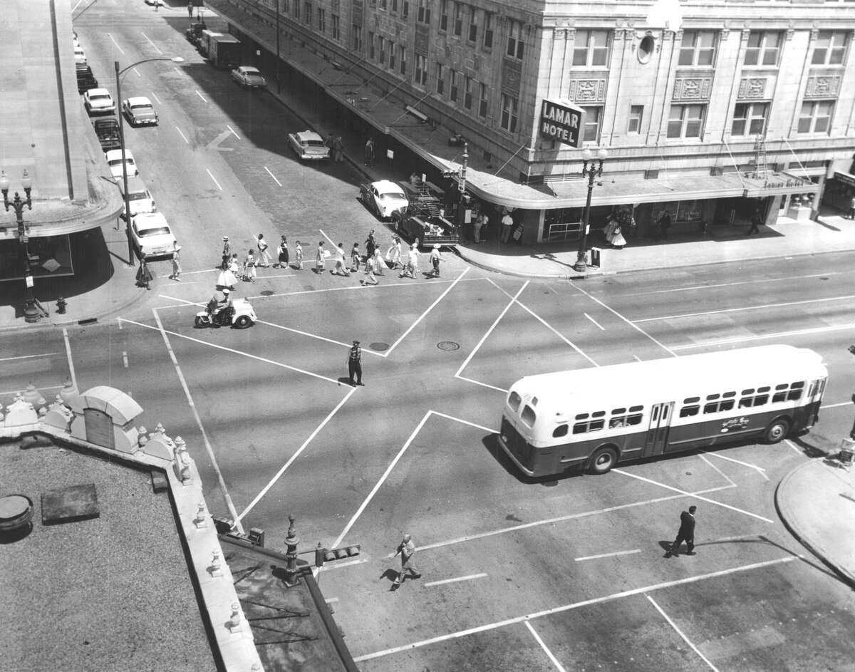 """A portion of the building, sans slipcovers, can be seen in the lower left corner of this photo.July 11, 1957: Houston motorists and pedestrians were about to get their first crack at the """"scramble"""" system of traffic management at Main and Lamar. Here, all traffic lights are red for 32 seconds while pedestrians cross the street at any direction. After a couple days, it became clear that motorists did not like it while pedestrians did. Drivers complained the holdup was causing traffic to back up in all directions and into adjoining intersections. More than a month later, the experiment came to an end, citing the backups and an increase in violations caused by impatient pedestrians unable to tolerate the longer wait at the intersections."""