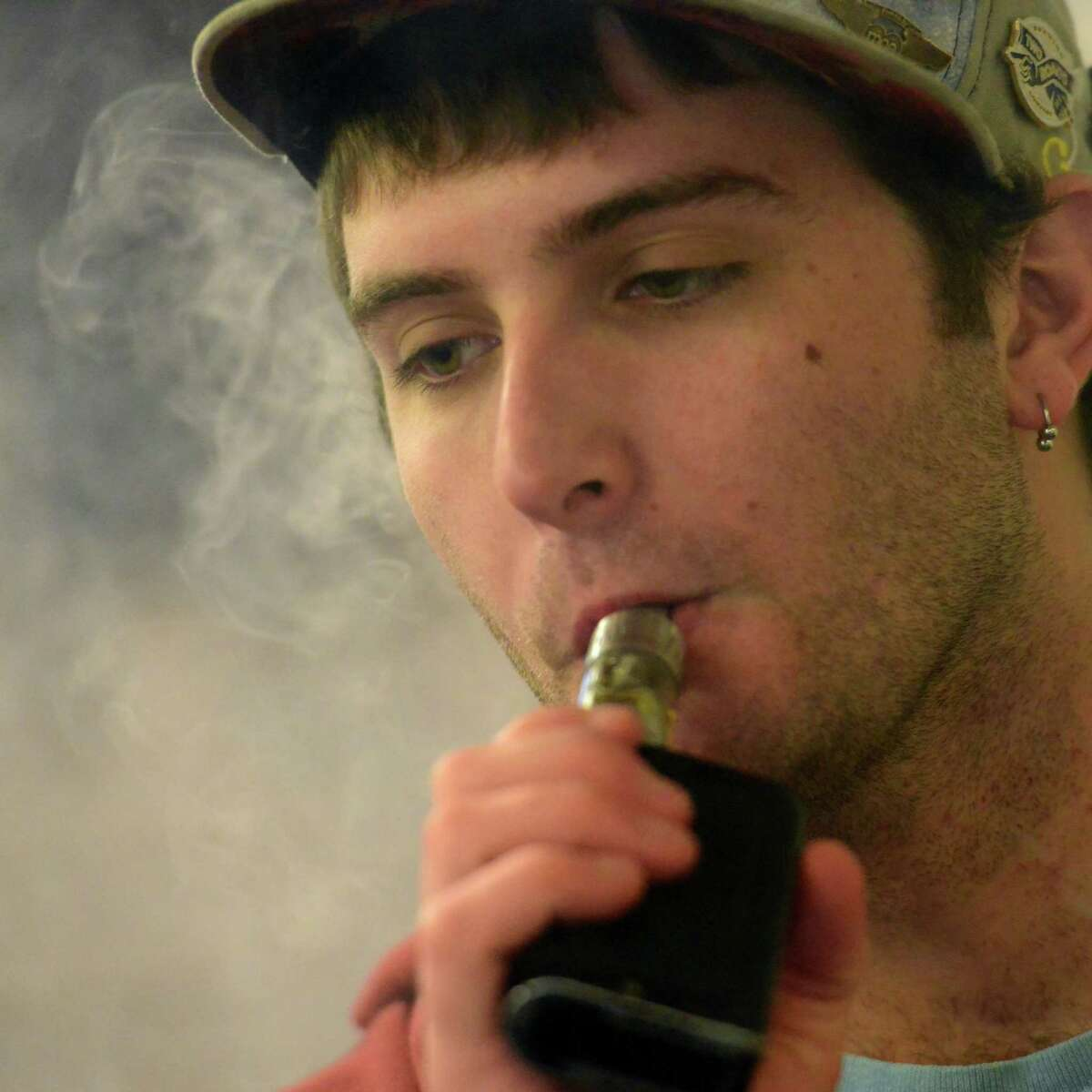 E-Stop E-Cigs co-owner Aidan Belmont vapes while at the shop on Post Road in Milford.