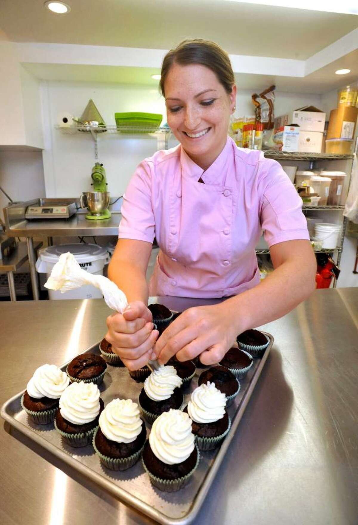 Kristen Mase, 26, frosts cupcakes at Sugar Hoot in New Milford, on Wednesday, July 21, 2010.