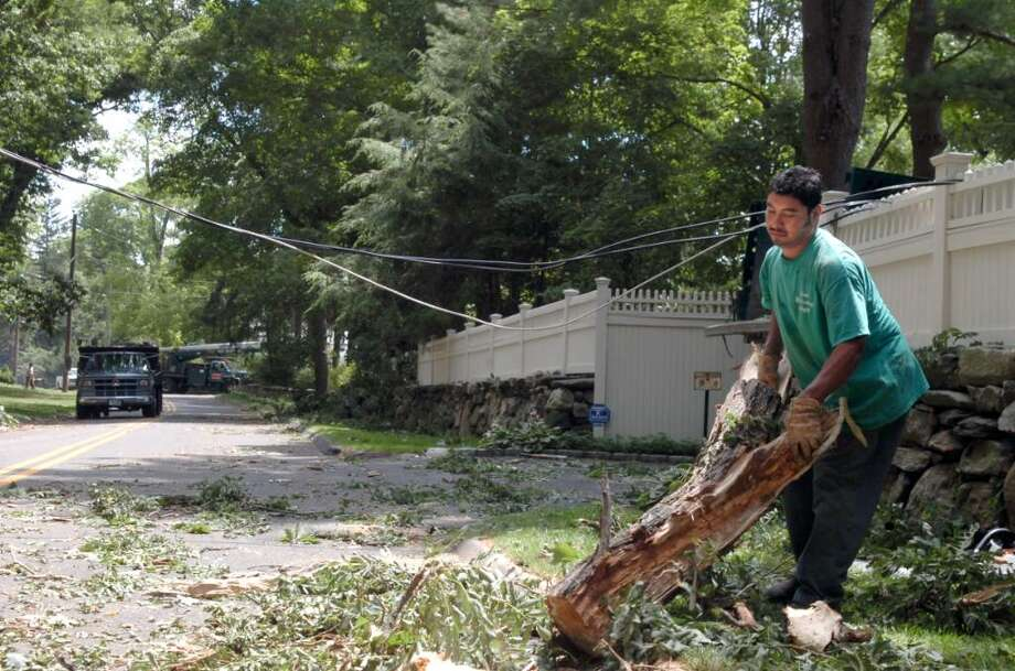 A man who identified himself only as Elder, of Stamford's Your Gardening Angel, clears the parts of trees that came down in Wednesday's storm, on Stanwich Road, on Thursday, July 22, 2010. Photo: Helen Neafsey / Greenwich Time