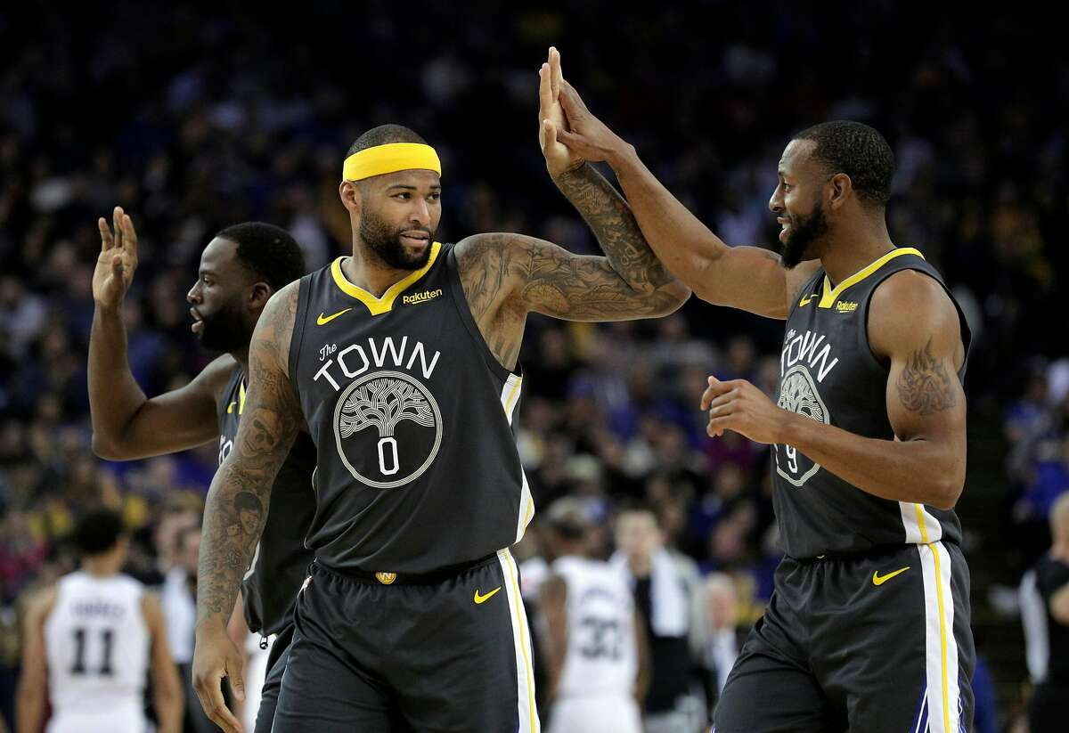 DeMarcus Cousins (0) high fives Andre Iguodala (9) after he dunked a shot in the first half as the Golden State Warriors played the San Antonio Spurs at Oracle Arena in Oakland, Calif., on Wednesday, February 6, 2019.