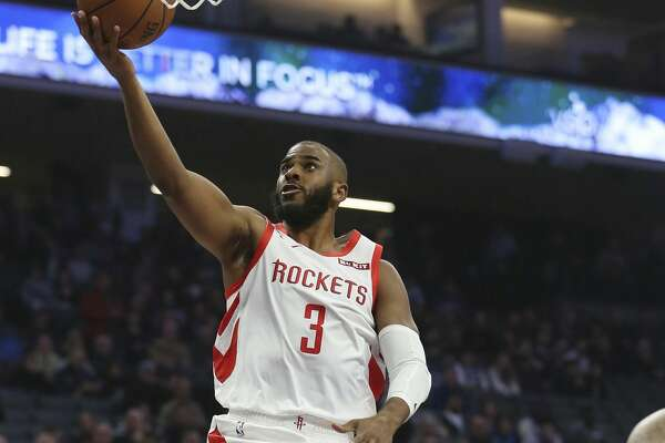 Houston Rockets guard Chris Paul, left, goes to the basket as Sacramento Kings guard De'Aaron Fox, rear, watches during the first quarter of an NBA basketball game Wednesday, Feb. 6, 2019, in Sacramento, Calif. (AP Photo/Rich Pedroncelli)