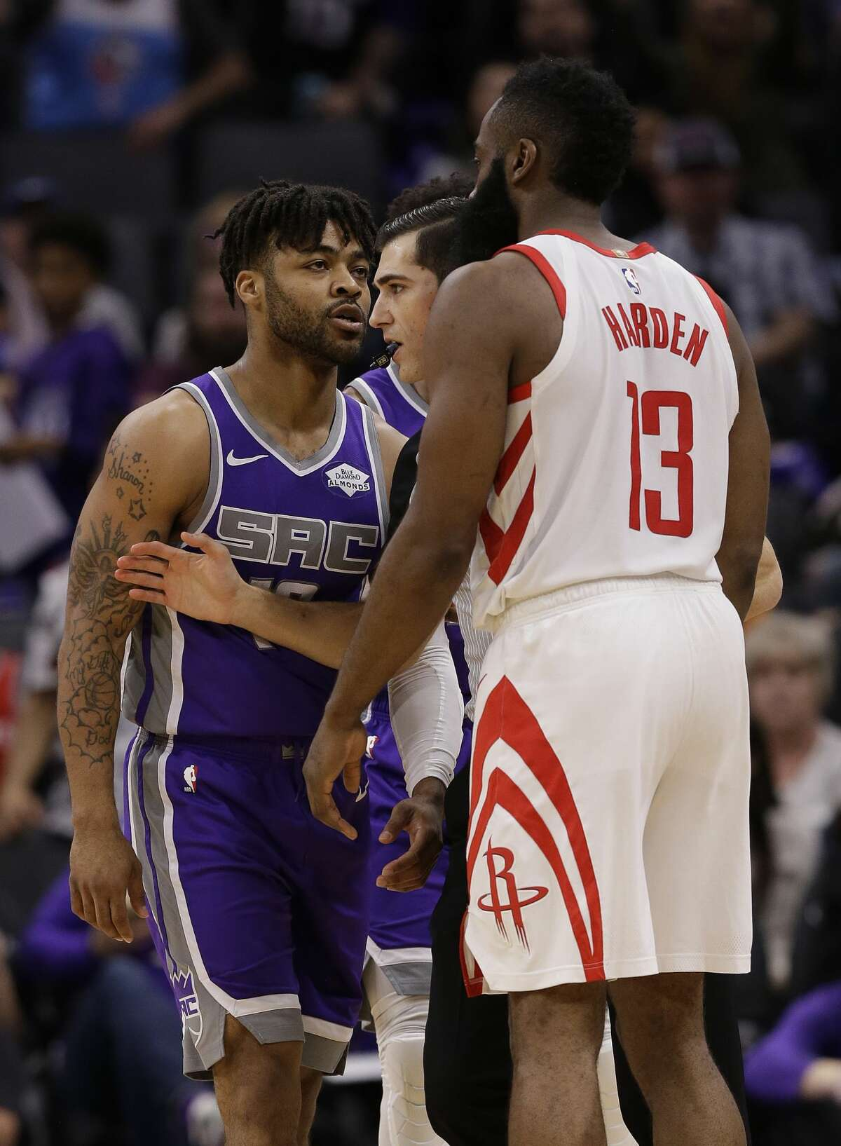 Referee Jason Goldenberg, center steps between Sacramento Kings guard Frank Mason III, left, and Houston Rockets guard James Harden as they exchanged heated words during the second half of an NBA basketball game Wednesday, Feb. 6, 2019, in Sacramento, Calif. The Rockets won 127-101. (AP Photo/Rich Pedroncelli)