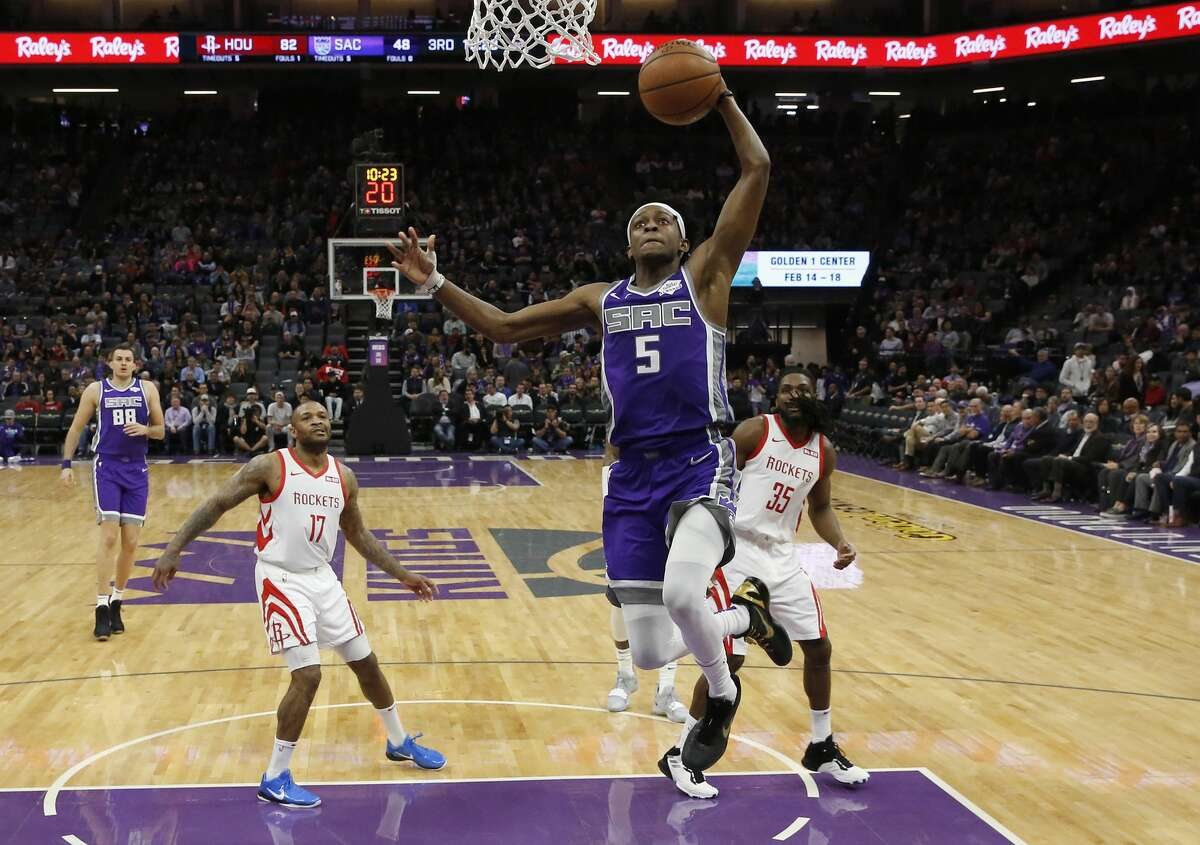 Sacramento Kings guard De'Aaron Fox, center, goes to the basket as Houston Rockets forwards PJ Tucker and Kenneth Faried, right, watch during the second half of an NBA basketball game Wednesday, Feb. 6, 2019, in Sacramento, Calif. The Rockets won 127-101. (AP Photo/Rich Pedroncelli)