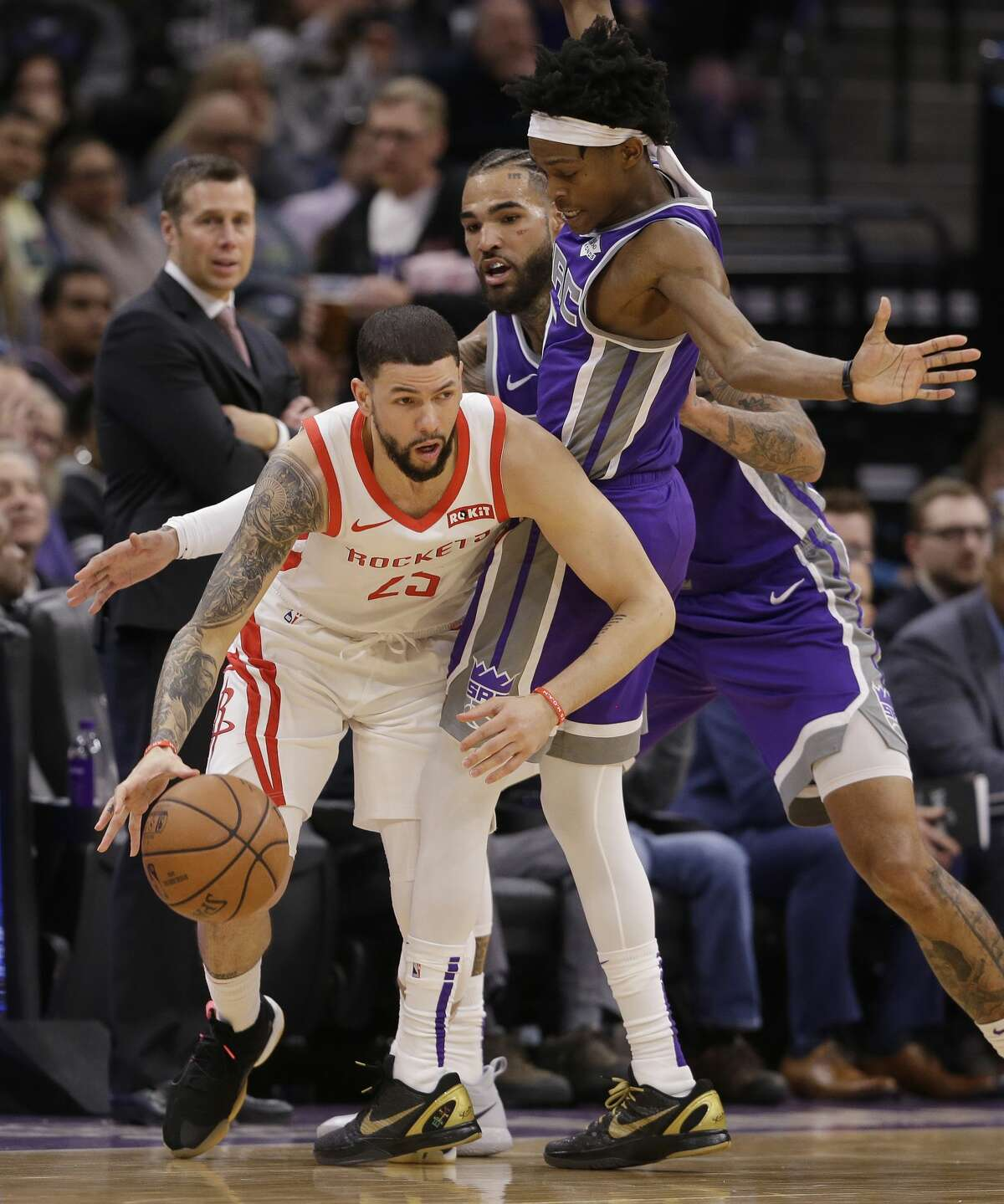 Houston Rockets guard Austin Rivers, left, tries to escape a double-team by Sacramento Kings' Willie Cauley-Stein, center, and De'Aaron Fox during the second half of an NBA basketball game Wednesday, Feb. 6, 2019, in Sacramento, Calif. The Rockets won 127-101. (AP Photo/Rich Pedroncelli)