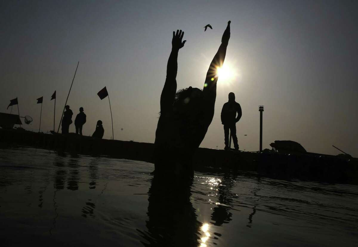 A Hindu devotee takes ritualistic dips at the confluence of three sacred rivers, Yamuna, the Ganges and Saraswati, during Kumbh Mela or Pitcher on Jan. 21, 2019. The Ganges river is considered a holy place yet it also riddled with pollution, including 1.2 billion pounds of plastic wastes filling its waters every year.