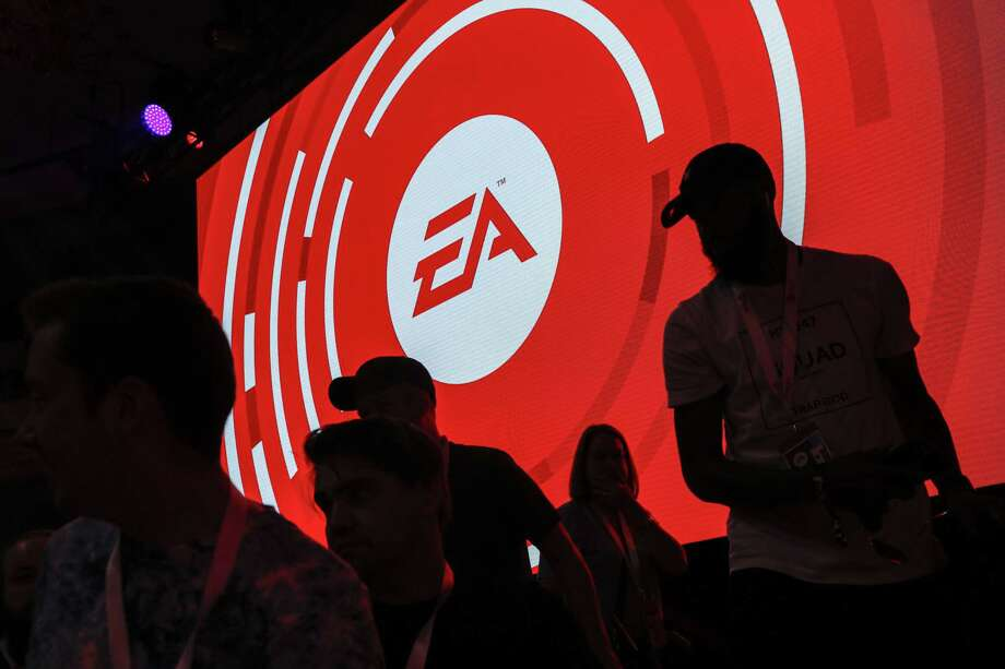 The silhouettes of attendees are seen standing in front of a Electronic Arts Inc. logo displayed on a screen during the company's EA Play event ahead of the E3 Electronic Entertainment Expo in Los Angeles on June 9, 2018. Photo: Bloomberg Photo By Patrick T. Fallon. / © 2018 Bloomberg Finance LP