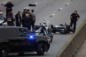 Houston Police officers investigate the scene of a motorcycle officer involved vehicle crash on the southbound lanes of Interstate 45, near North Main Street Thursday, Feb. 7, 2019, in Houston.