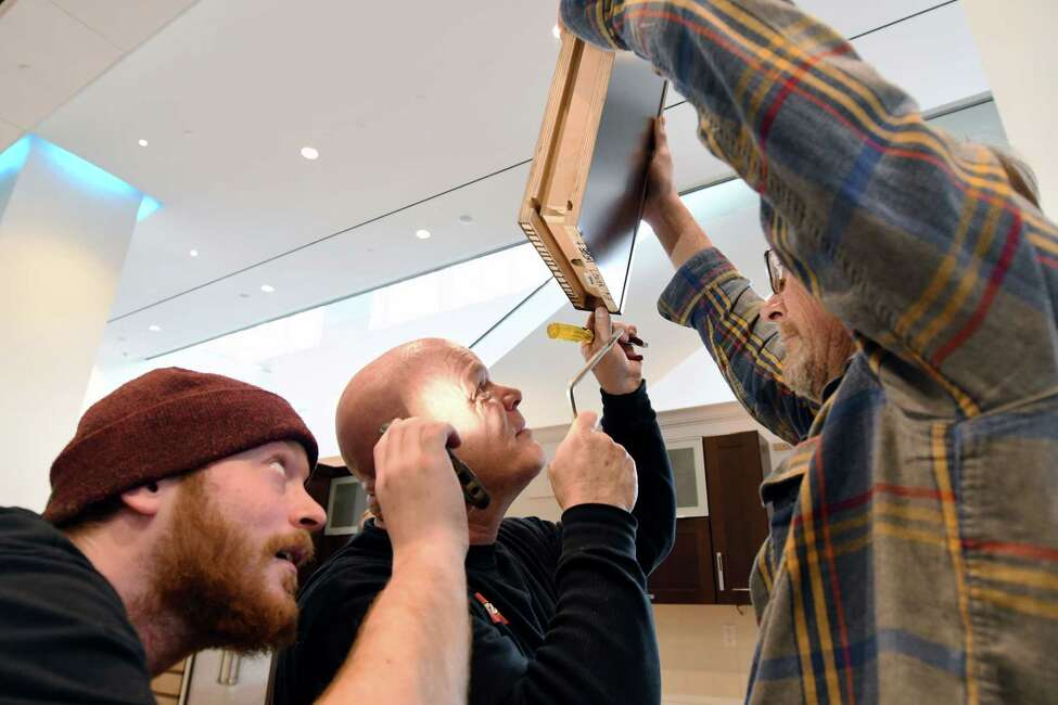 From left, Justin Sutherland, Glenn Sutherland and Dave Gratto of Creatacor work on wiring during setup for the Times Union Home Expo Thursday, Feb. 7, 2019 at the Albany Capital Center in Albany, NY. (Phoebe Sheehan/Times Union)