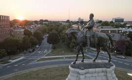 In this July 31, 2017 photo, the sun sets behind the statue of confederate General Robert E. Lee on Monument Avenue in Richmond, Va. Virginia has become more diverse and socially liberal in recent years. But the state continues to struggle with mindsets shaped by its turbulent racial history. When a racist photo was discovered last week on Gov. Ralph Northam's 1984 medical school yearbook page, it exposed how much deeply embedded racism still lurks in the state. (AP Photo/Steve Helber)