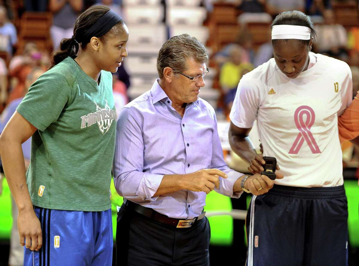 UConn coach Geno Auriemma with Maya Moore (left) and Tina Charles (right). Moore is stepping away from professional basketball.