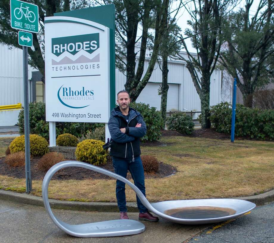Domenic Esposito stands with an 800-pound spoon sculpture, outside the headquarters of Coventry, R.I. headquarters of Rhodes Pharmaceuticals. He staged a similar protest on June 22, 2018, outside the downtown Stamford, Conn. headquarters of Purdue Pharma. Photo: Hand-out / Domenic Esposito / Domenic Esposito