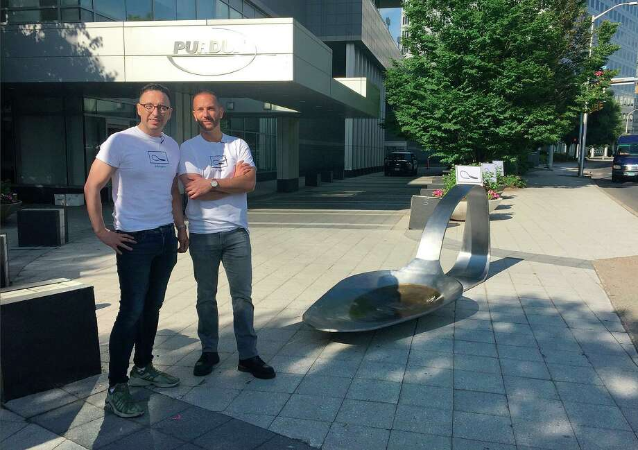 FILE - In this June 22, 2018 file photo, art gallery proprietor Luis Alvarez, left, and sculptor Domenic Esposito, right, stand beside an 800-pound sculpture of a bent, burnt heroin spoon placed in front of the Stamford, Conn., headquarters of Purdue Pharma to protest the company's manufacture of opioids. A judge signed an order Monday, Aug. 27, 2018, that Esposito can retrieve the sculpture from Stamford police, saying the process could take days. (Susan Dunne/Hartford Courant via AP, File) Photo: Susan Dunne / Associated Press / Hartford Courant