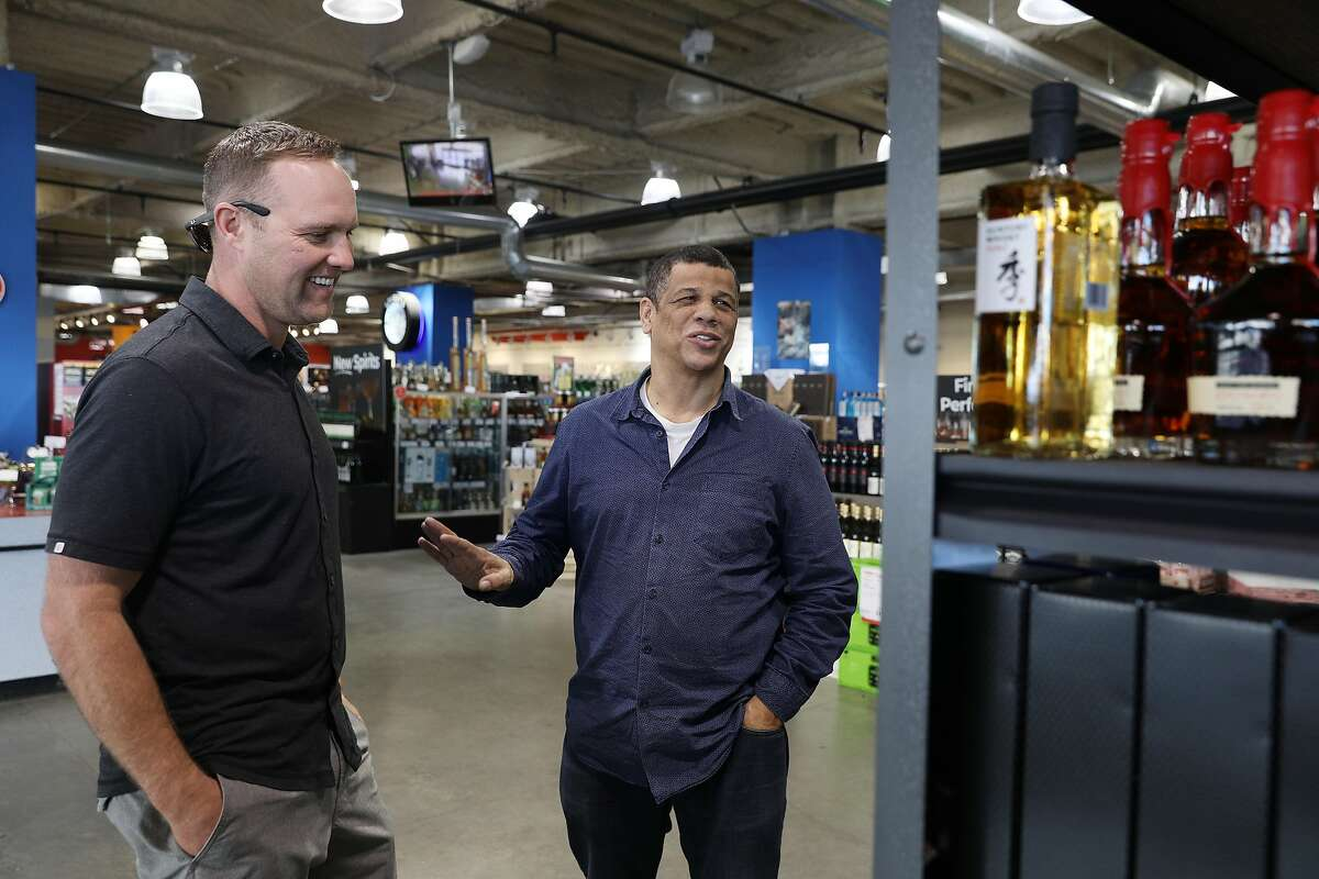 Glen Collins (right), store manager, demonstrates the interactive, voice-activated shopping assistant, SmartAisle, to customer Tyler Ridgley (left) of Monterey at a BevMo! store on Wednesday, February 6, 2019 in Oakland, Calif.