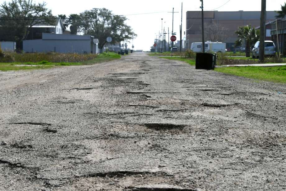 Pot holes litter Sabine Pass's 9th Avenue on Thursday. Residents of the coastal community say neglected roads are a major problem in the area. Sabine Pass school can be seen in the background. Photo taken Thursday, 2/7/19 Photo: Guiseppe Barranco/The Enterprise