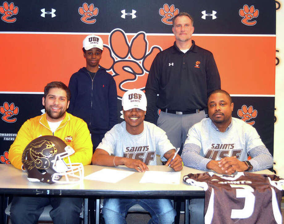 Edwardsville senior Dionte Rodgers, seated center, will play college football for St. Francis University. He is joined by his family, St. Francis assistant coach Brian Bonds and EHS coach Matt Martin. Photo: Scott Marion/Intelligencer