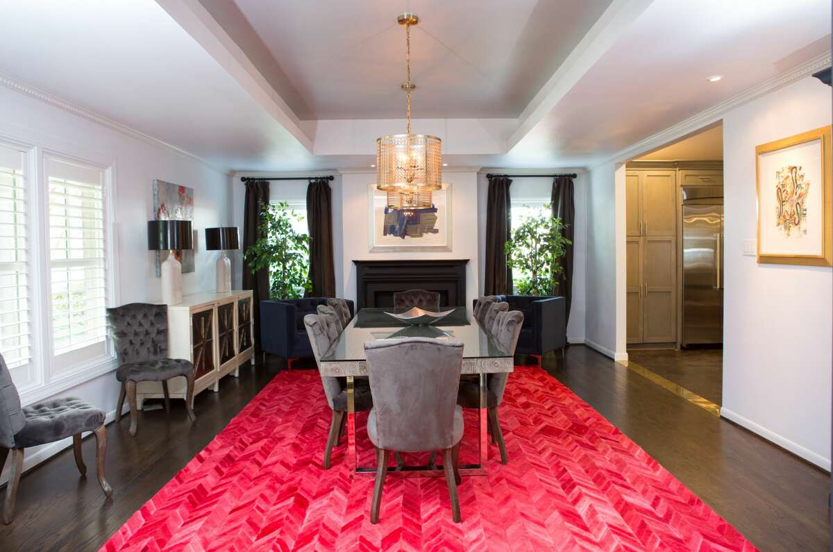 The otherwise neutral dining room gets a bold burst of color with a cowhide rug, stitched together herringbone style and dyed bright red.