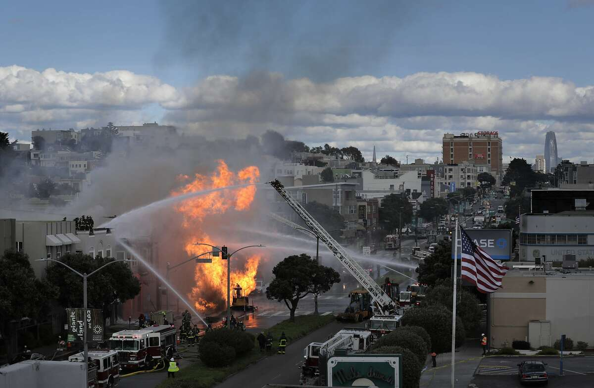 San Francisco firefighters work a gas line explosion and fire that burned several structures on Geary Blvd. in San Francisco, Calif., on Wednesday, February 6, 2019. The gas line was capped after about two hours burning uncontrolled.