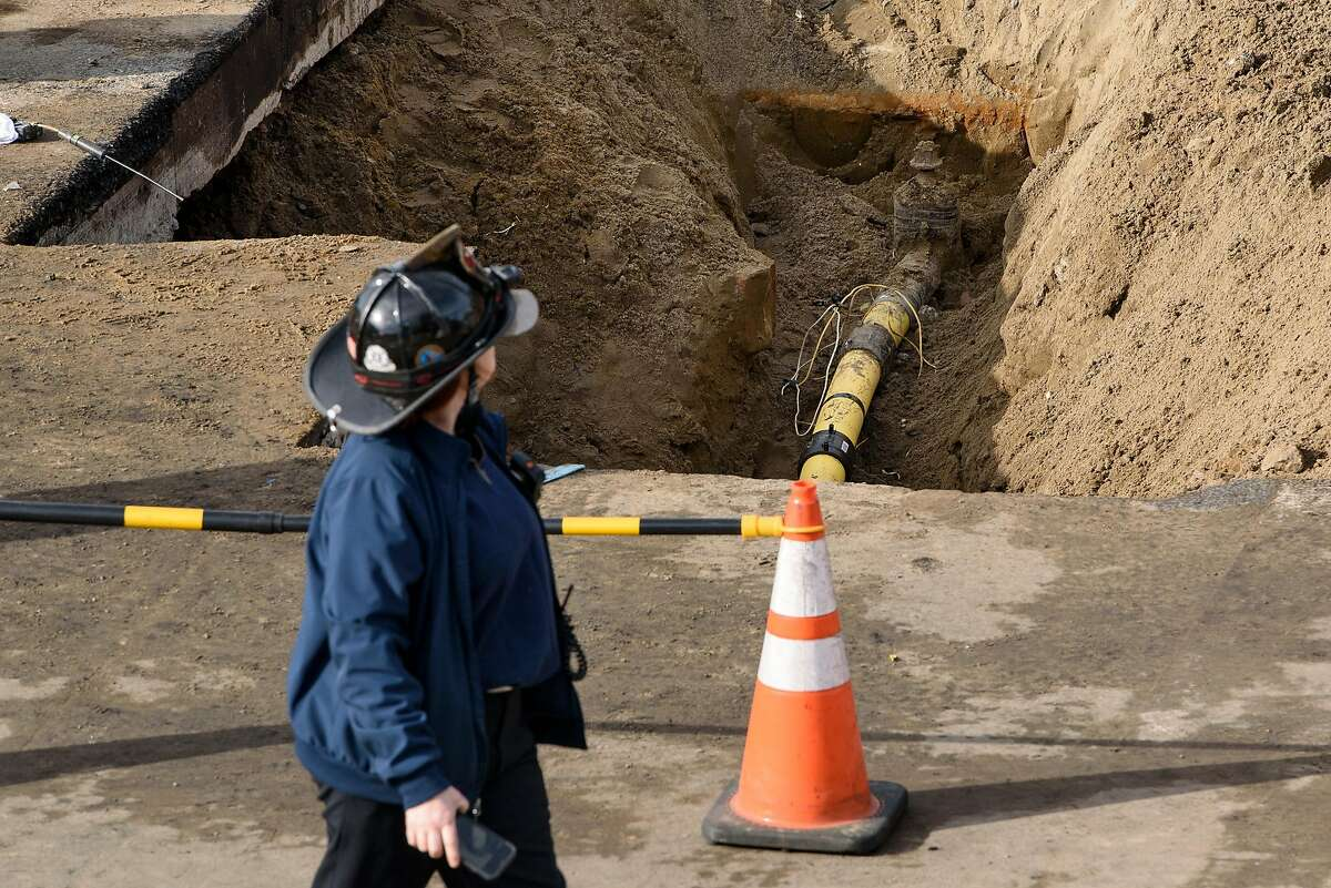A fire department official walks past the exposed PG&E pipeline at the site of a gas fire caused when contractors installing fiber optic cable hit the line, in San Francisco, Calif., on Thursday, February 7, 2019.