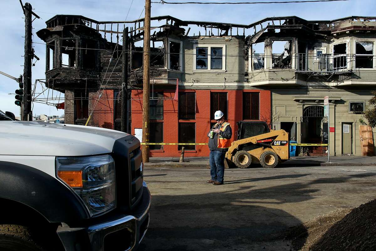 A PG&E worker stands in front of the burnt out Hong Kong Lounge II restaurant which was the site of a gas fire caused when contractors installing fiber optic cable hit a PG&E pipeline, in San Francisco, Calif., on Thursday, February 7, 2019.
