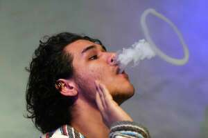 Angel Salcedo, of Port Chester, N.Y., blows a ring while vaping at CLOUDS Vapors & Lounge in the Byram section of Greenwich, Conn. Thursday, Feb. 18, 2016. There is propsed legislation for makers of liquid nicotine to childproof their containers, which could be just the start of an effort by Connecticut lawmakers to regulate the electronic cigarette industry and its marketing to kids.