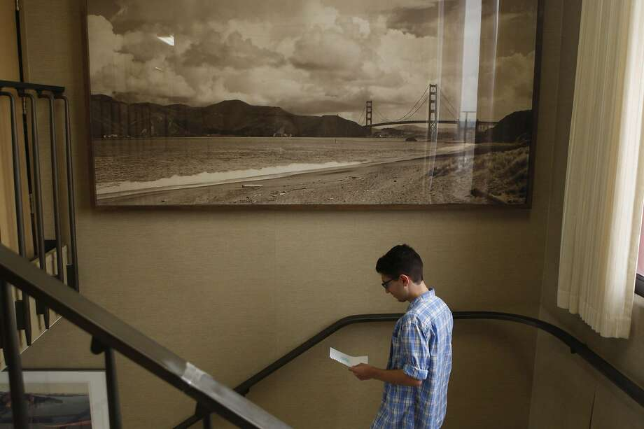 Manuel Gamboa III holds a picture that a child drew for him at the Golden Gate Bridge, Highway and Transportation District board meeting in 2018. His parents have attended almost every board meeting since his brother Kyle jumped in 2013, and when they can't attend he goes in their place. For his parents, these meetings are a way to cope with loss through activism, but for Manuel the meetings bring back the hard memories. Photo: Liz Moughon / The Chronicle