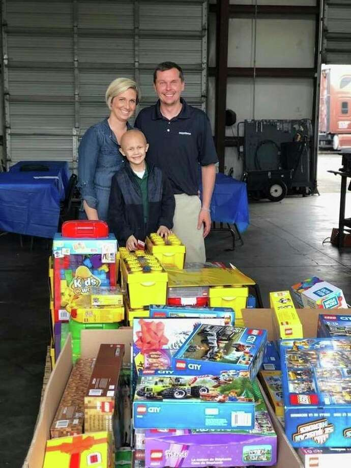 Reece Kolar is shown here with his parents, Rachel and Steve, and a donation of Legos from Steve's employer, W.W. Williams. (Courtesy Photo)