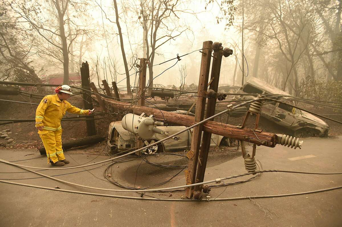 (FILES) In this file photo taken on November 10, 2018 CalFire firefighter Scott Wit surveys burnt out vehicles near a fallen power line on the side of the road after the Camp fire tore through the area in Paradise, California. - Obsolete installations, negligence, a culture of profit at the expense of safety and even