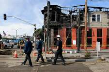 Fire department officials walk in front of the burnt out Hong Kong Lounge II restaurant which was the site of a gas fire caused when contractors installing fiber optic cable hit a PG&E pipeline, in San Francisco, Calif., on Thursday, February 7, 2019.