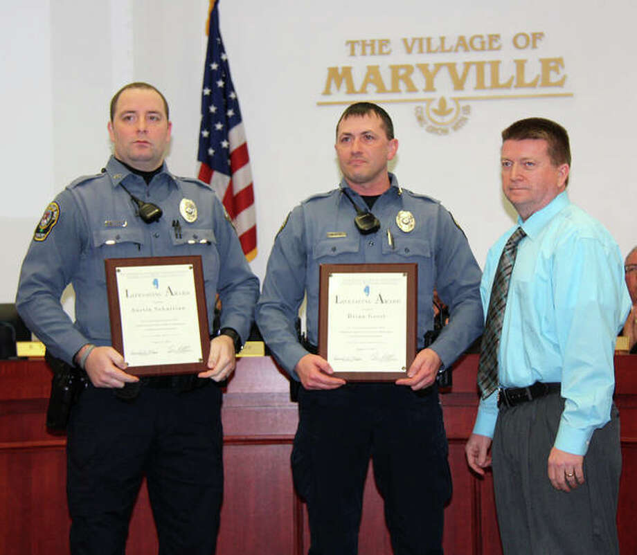 Maryville police officers Austin Sebastian, left, and Brian Gessi, center, recieve lifesaving awards from their chief, Rob Carpenter, right, during Wednesday's village board of trustees meeting. Photo: Charles Bolinger | The Intelligencer
