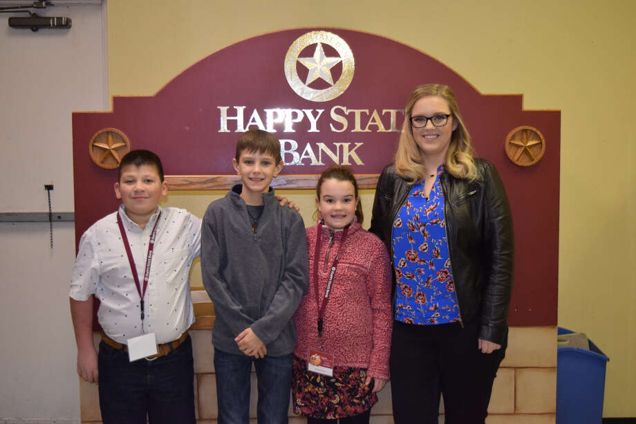 Aleks Ludlum, Mason King and Brynae Harrison, all tellers, stand with Jordan Dunlap, with Happy State Bank, after a recent Kids' Bank Day at PCA. Photo: Ellysa Harris/Plainview Herald