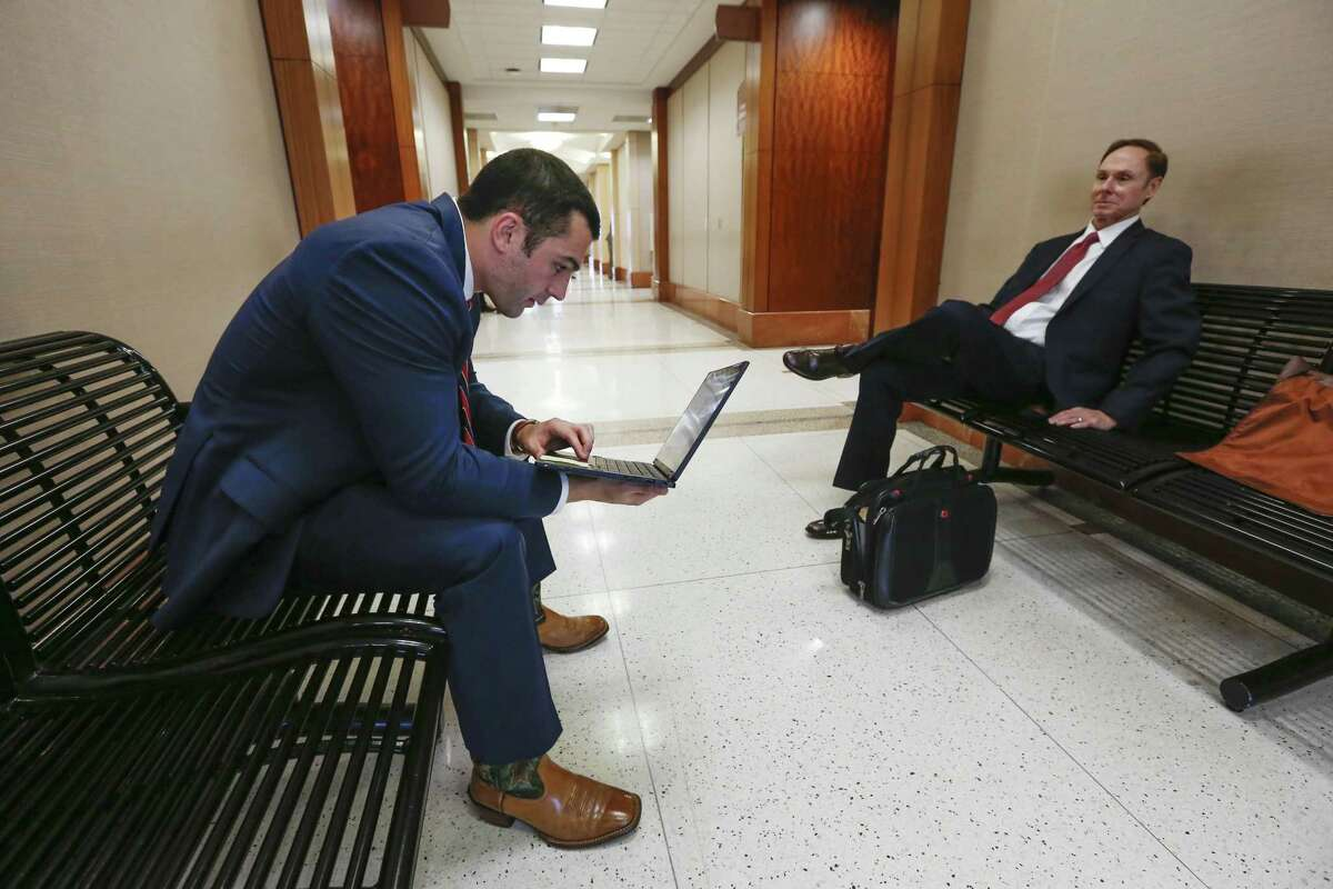 Assistant District Attorney Michael Hanover, left, talks to Tom Lewis outside the 174th Criminal District Court on Wednesday, Feb. 6, 2019, in Houston. Harris County District Attorney Kim Ogg is asking Commissioners Court for 100 new prosecutors to help clear a felony case backlog that was exacerbated by Hurricane Harvey.