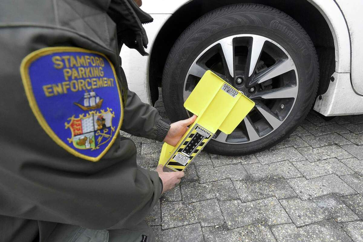 A Stamford Parking Enforcement Officer demonstrates use of a self-releasing electronic boot on Thursday, Feb. 7, 2019 in Stamford, Connecticut.