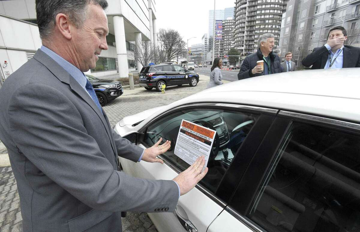 Transportation Bureau Chief Jim Travers places a sticker onto a window that notifies the owner that their vehicle has been disabled with the new self-releasing electronic boot on Thursday, Feb. 7, 2019 in Stamford, Connecticut. The city has deployed the new boot device to go after almost 5,700 scofflaws in Stamford who have about 28,000 parking tickets and owe the city almost $2.1 million.