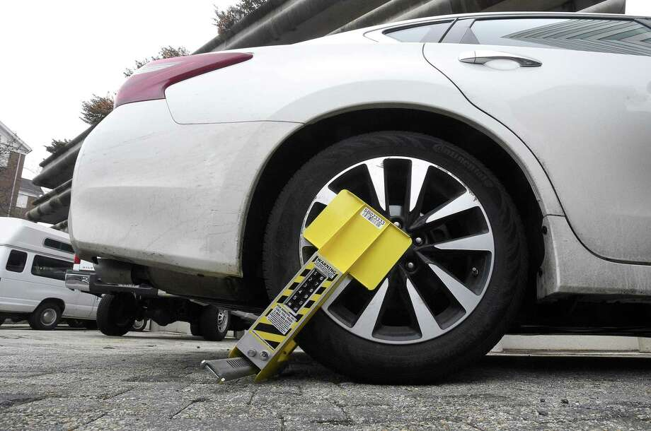 A vehicle is disabled with a new self-releasing electronic boot in Stamford. Photo: Matthew Brown / Hearst Connecticut Media / Stamford Advocate