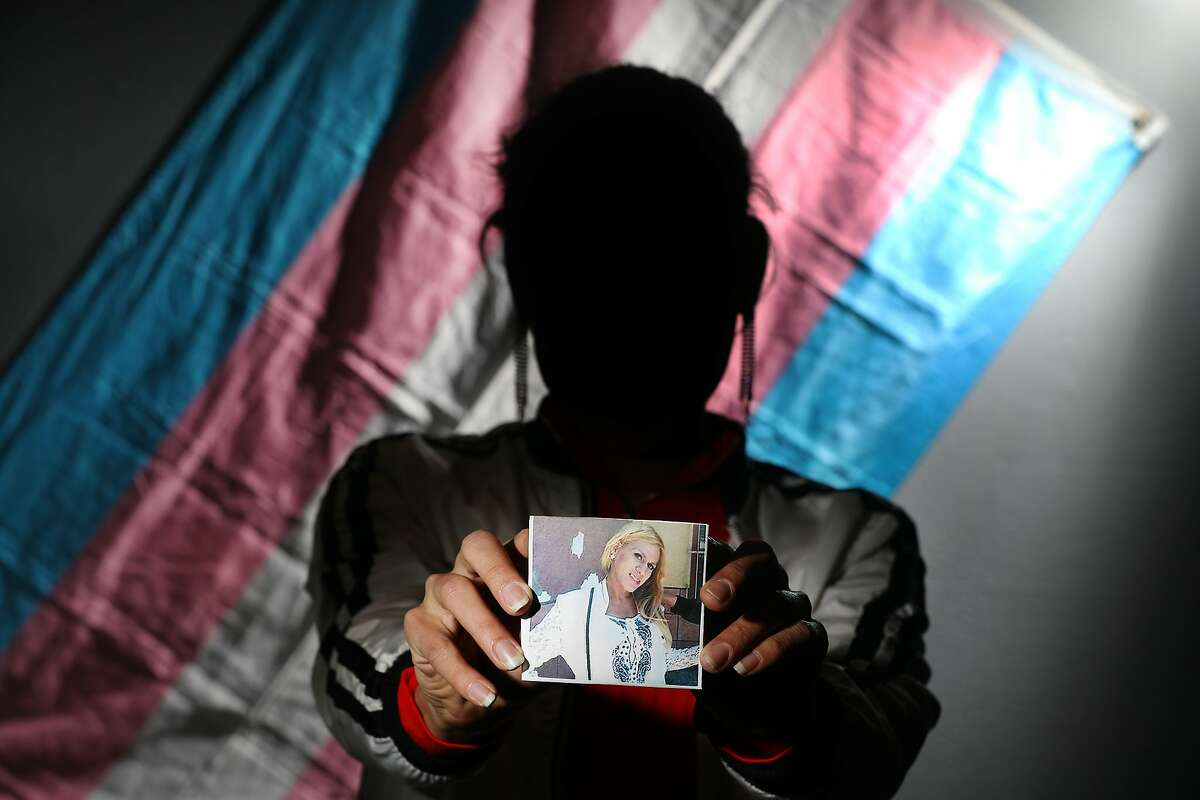 """""""Charlotte"""" holds a photo of her friend Roxana Hernandez as she stands for a portrait at El/La Para TransLatinas in front of a transgender pride flag on Wednesday, January 22, 2019 in San Francisco, Calif."""