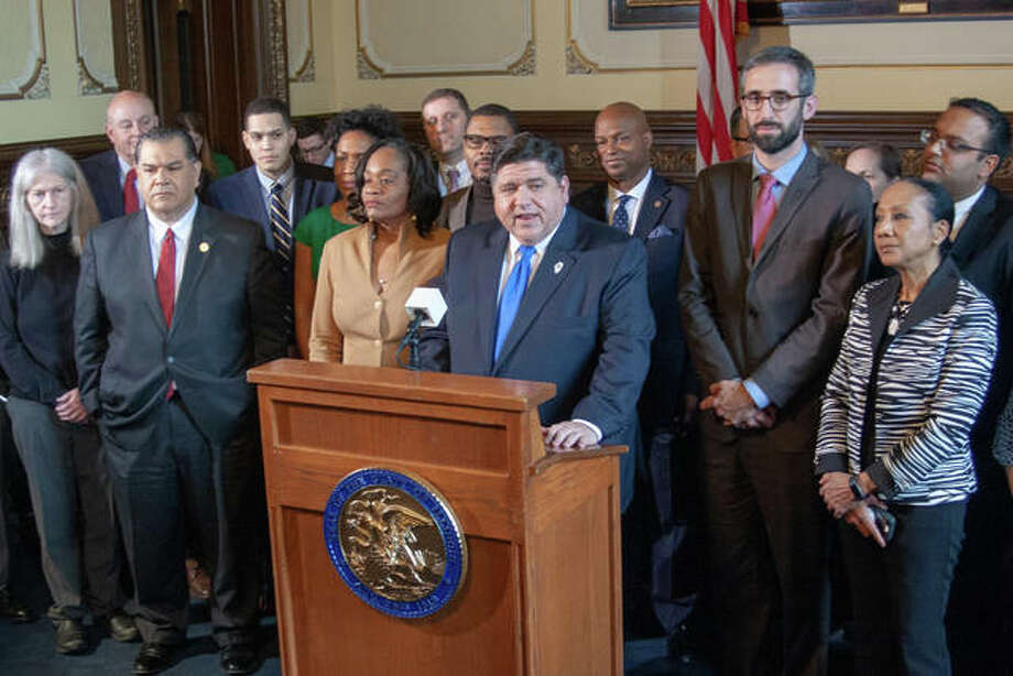 Gov. J.B. Pritzker is joined by minimum wage advocates in his office for a news conference Thursday following the Senate's vote to approve Senate Bill 1, which raises the state's minimum wage to $15 per hour over a 6-year period. He was joined by Sen. Kimberly Lightford (left), D-Maywood, the bill's Senate sponsor, and Rep. Will Guzzardi (right), D-Chicago, the bill's House sponsor. Photo: Capitol News Illinois Photo By Jerry Nowicki