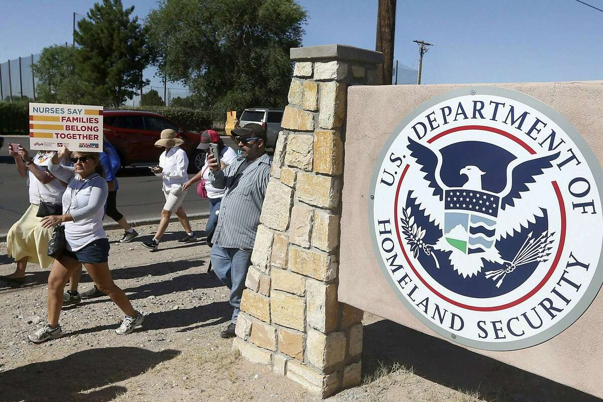 """Protesters walk past the El Paso Processing Center, in El Paso, Texas, in 2018. The Biden administration has dropped a Trump policy of threatening immigrants who take public benefits with deportation. Continuing to defend the 2019 policy """"is neither in the public interest nor an efficient use of limited government resources,"""" the Department of Homeland Security said."""
