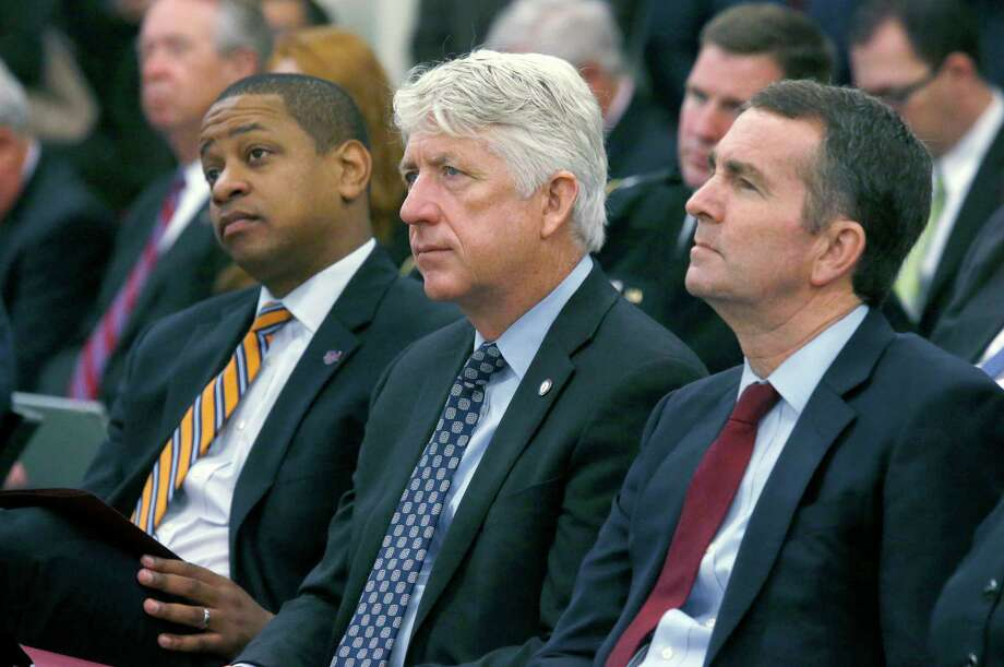 FILE - In this Dec. 18, 2017 file photo, from left, Lt. Governor-elect Justin Fairfax, Attorney General-elect Mark Herring and Governor-elect Ralph Northam listen as Virginia Governor Terry McAuliffe addresses a joint meeting of the House and Senate money committees at the Pocahontas Building in Richmond, Va.  With Virginia's top three elected officials engulfed in scandal, fellow Democrats were rendered practically speechless, uncertain of how to thread their way through the racial and sexual allegations and their tangled political implications.  (Bob Brown/Richmond Times-Dispatch via AP) Photo: Bob Brown / Richmond Times-Dispatch