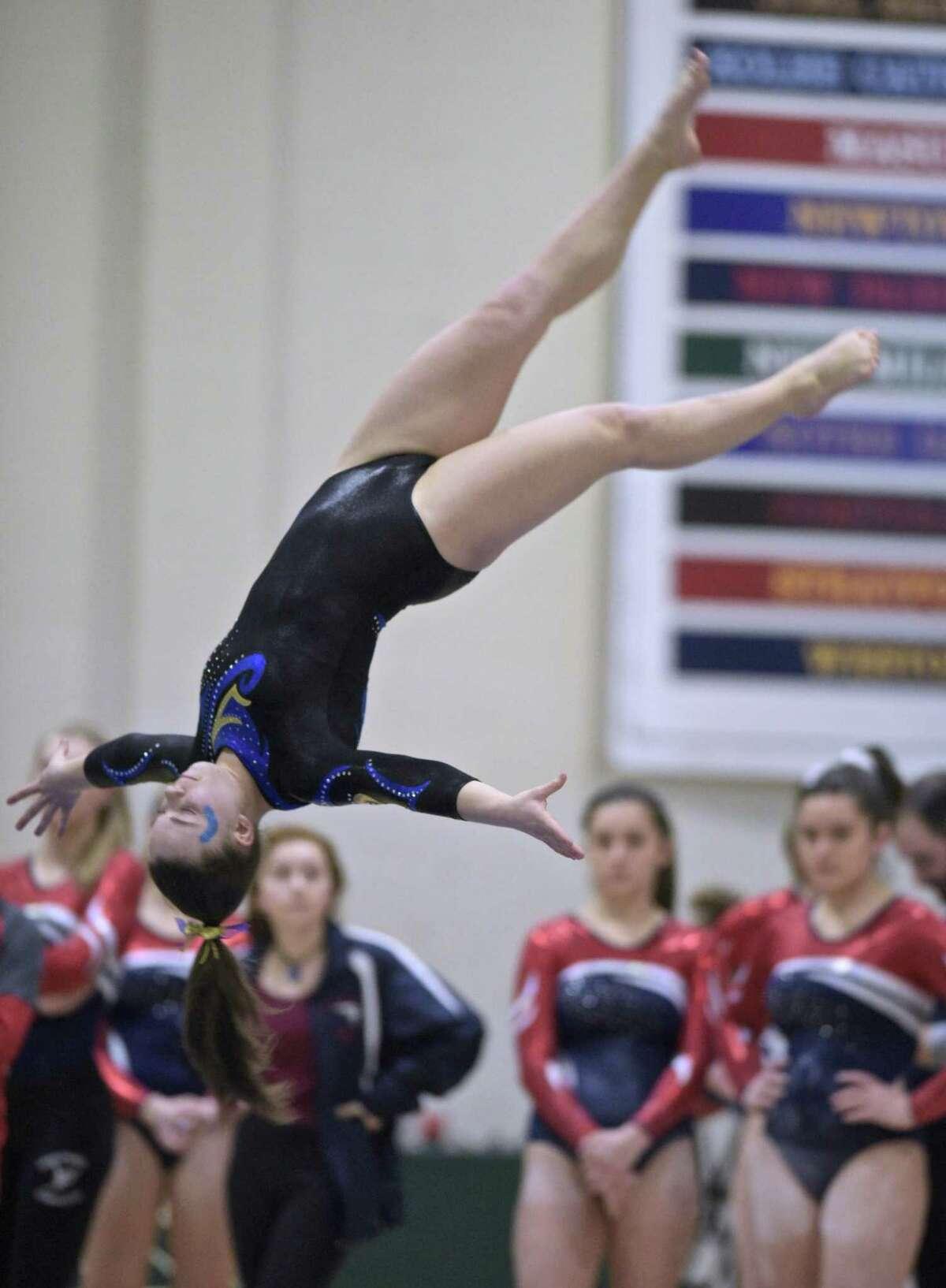 Newtown's Hannah Jojo dismounts from the beam during the SWC girls high school gymnastics championships at New Milford High School, New Milford, Conn, Thursday, February 7, 2019.